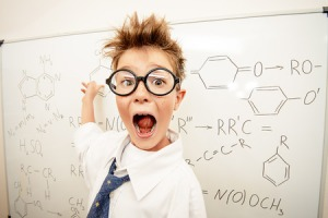 44127272 - funny schoolboy in big glasses standing by the school board and shouting. chemistry. science and education.