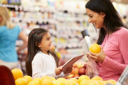 42270022 - mother and daughter at fruit counter in supermarket with list